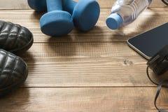 Equipmen de sport et de forme physique avec des espadrilles, des haltères, la serviette et des écouteurs sur le conseil en bois V Photos stock