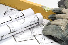 Equipment for Builder. Builder's equipment - blueprints of architecture interior, builder's level and protective gloves Royalty Free Stock Photography