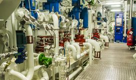 Equipment, cables, pipes and valves in engine room of a ship pow royalty free stock images
