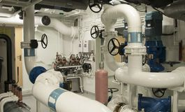 Equipment, cables, pipes and valves in engine room of a ship pow stock photo