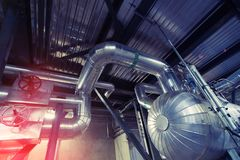 Equipment, cables and piping as found inside of a modern industrial power plant. stock images