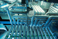 Equipment, cables and piping inside of a modern industr Stock Photos