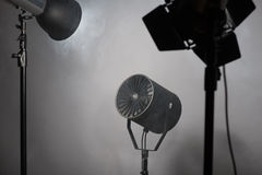 Equipment of cinematography. Three projectors standing enveloped in smoke. Isolated on grey background stock image
