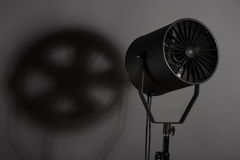 Equipment of cinematography. Turned on spotlight standing with the shade. Isolated on grey background royalty free stock photos