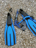 Equipment for the divers. Diving mask, snorkel, harpoon and fins on stone beach Royalty Free Stock Images