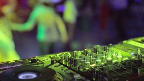 Equipment of DJ, male hands control audio while people dance relax on dancefloor. Stock footage stock footage