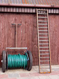 Equipment on the farm. Close-up. Wooden wall and  leaning ladder Stock Photos