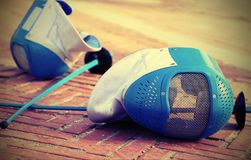 Equipment fencing mask and foil resting on the ground after the stock images