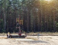Equipment on the field against the backdrop of the forest for the extraction of oil and gasoline, extraction of petroleum stock photos