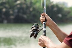 Equipment for fishing. Close-shot of human hands holding a fishing-rod on the foreground Stock Image