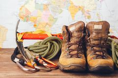 Equipment for high-altitude climbing: boots, sport ropes, carbines on the background of a geographical map. Copy space stock photos