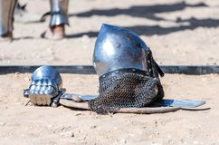 Equipment knight - the participant in the knight festival - shield, sword, helmet and glove lie on the ground  near the lists. Equipment knight - the participant Stock Photo