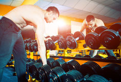 Equipment for muscles. Young sportive man taking heavy sport equipment in gym Royalty Free Stock Images