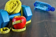 The equipment needed for fitness on board. Dumbbell and snacks. Fitness equipment. Dumbbell, towel, banana apple and weight loss meter Stock Image
