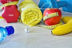 The equipment needed for fitness on board. Dumbbell and snacks. Fitness equipment. Dumbbell, towel, mineral water, banana, apple and weight loss meter. And the Stock Images