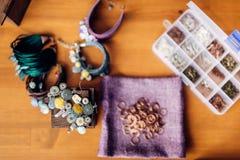 Equipment for needlework, bracelets, top view. Box with equipment for needlework, bracelets on wooden table, top view. Handmade jewelry. Handicraft, bijouterie Royalty Free Stock Image