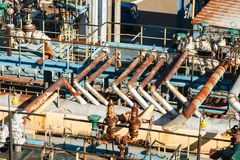 The equipment of oil refining. Industrial zone,The equipment of oil refining,Close-up of industrial pipelines of an oil-refinery plant,Detail of oil pipeline stock photography