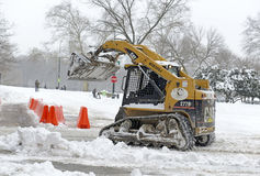 Equipment with plow cleans snow on the street, New York City Stock Photo