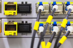 Equipment of radio base station close-up, blue and yellow optic patch cords. Royalty Free Stock Image