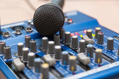 The equipment for recording. Microphone lying on sound mixing Board Stock Image