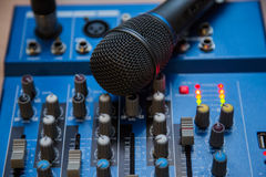 The equipment for recording. Microphone lying on sound mixing Board Stock Photo