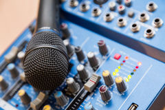 The equipment for recording. Microphone lying on sound mixing Board Stock Photography