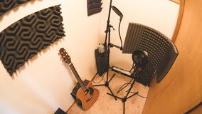 Equipment in a recording studio booth. Guitar, microphones, and audio treatment panels in a recording studio room Stock Photography