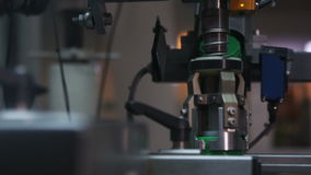 Equipment Turns Fast Cap to Bottle with Motor Oil. Closeup camera shows automated steel equipment turns fast green round cap to bottle with motor oil stock video footage