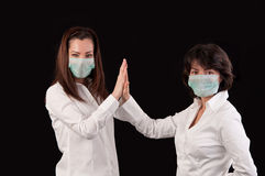 Equipo acertado de doctores de sexo femenino que dan el alto cinco y risa Foto de archivo libre de regalías