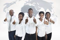 Equipo africano del negocio con el mapa del mundo, pulgares para arriba Fotos de archivo libres de regalías