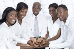 Equipo africano del negocio que presenta con las manos abiertas Fotos de archivo libres de regalías