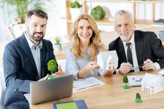 Equipo alegre de agentes inmobiliarios que sonríe mientras que se sienta en la tabla junto fotografía de archivo libre de regalías