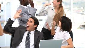 Equipo alegre del negocio que mira un ordenador portátil metrajes
