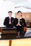 Equipo asiático chino de la recepción en el mostrador del hotel foto de archivo libre de regalías