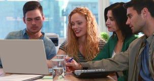Equipo casual del negocio usando el ordenador portátil durante la reunión metrajes
