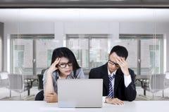 Equipo confuso del negocio con el ordenador portátil en el escritorio Fotos de archivo