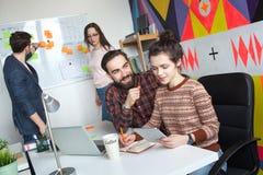 Equipo creativo de cuatro colegas que trabajan en oficina moderna Fotografía de archivo libre de regalías