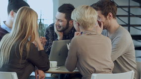 Equipo creativo de diseñadores jovenes que trabajan junto en su oficina durante la reunión informal metrajes