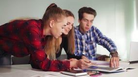 Equipo creativo del negocio de tres personas que se encuentran en una oficina moderna Una mujer que señala su lápiz en el papel a almacen de metraje de vídeo