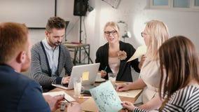 Equipo creativo del negocio en la tabla en una oficina de lanzamiento moderna El líder de sexo femenino explica los detalles del  fotografía de archivo libre de regalías