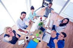 Equipo creativo del negocio que gesticula los pulgares para arriba en una reunión Fotografía de archivo