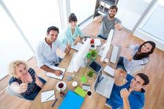 Equipo creativo del negocio que gesticula los pulgares para arriba en una reunión Imágenes de archivo libres de regalías