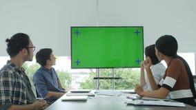 Equipo creativo del negocio que mira la pantalla verde en la sala de conferencias almacen de video
