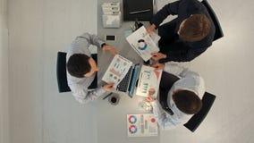 Equipo creativo que exhibe cartas con el ordenador portátil y almacen de metraje de vídeo