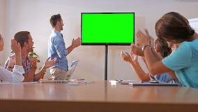 Equipo creativo que mira la televisión con la pantalla verde almacen de metraje de vídeo