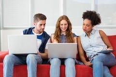 Equipo creativo usando los ordenadores portátiles y la tableta digital imagen de archivo