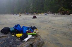 Equipo de acampada en un canto rodado en la playa en la niebla fotografía de archivo