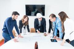 Equipo de arquitectos que presentan proyecto de construcción Dirige imagen de archivo