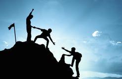 Equipo de ayuda que sube trabajar, concepto del éxito
