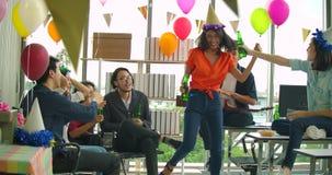 Equipo de baile y de divertirse de celebrar con la tostada y de tintinear de la gente joven aumentando los vidrios en su oficina almacen de metraje de vídeo